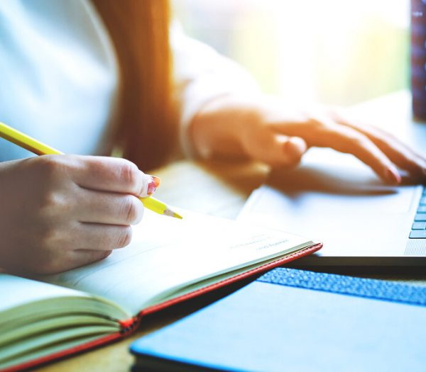 Woman hand with pencil writing on notebook. making notes in notebook with pencil. People writing on notebook and work on wooden table